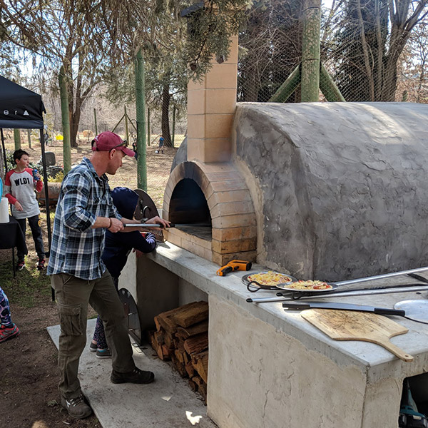 A man cooking pizza in a woodfired oven