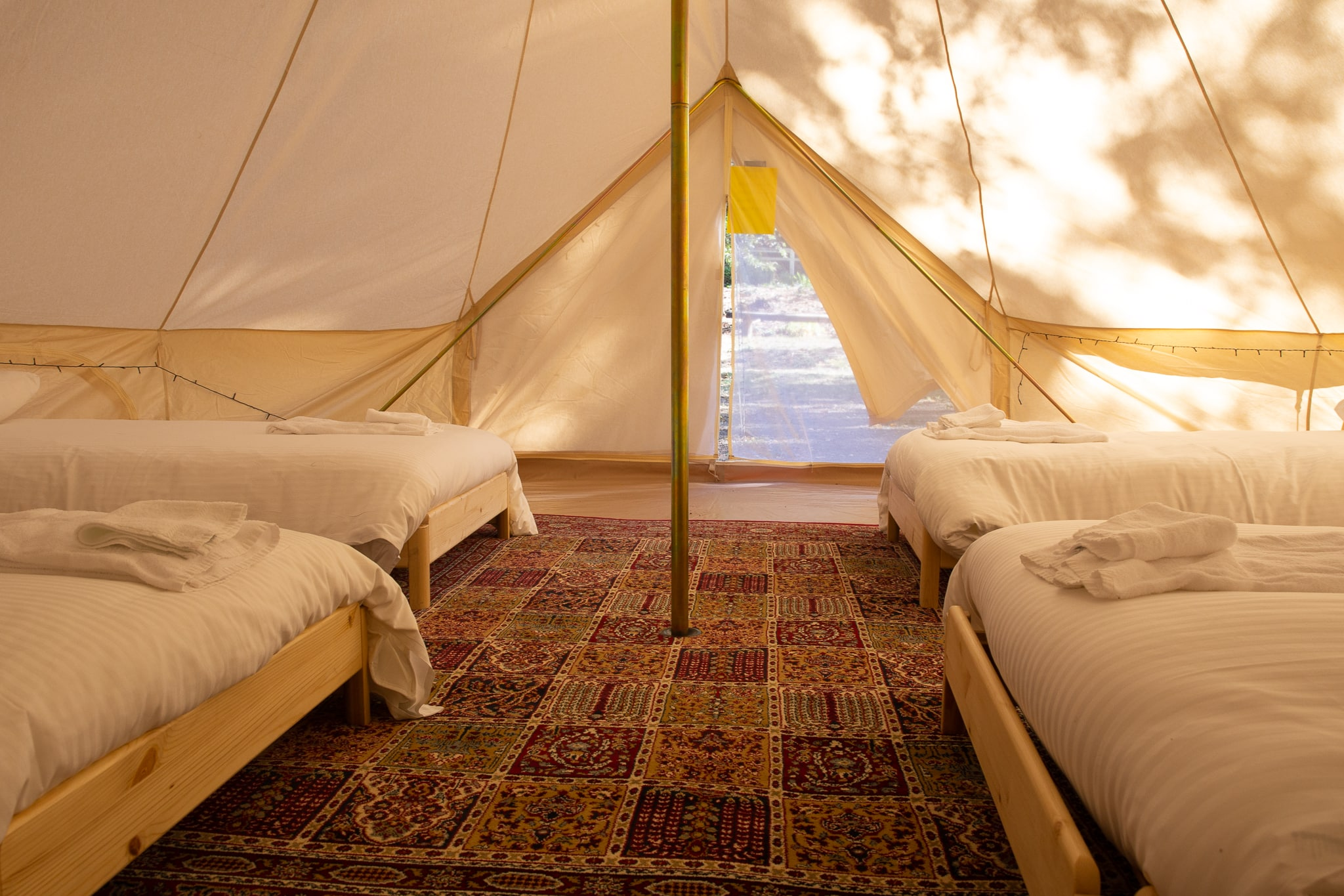 Belle glamping tent with rug and beds